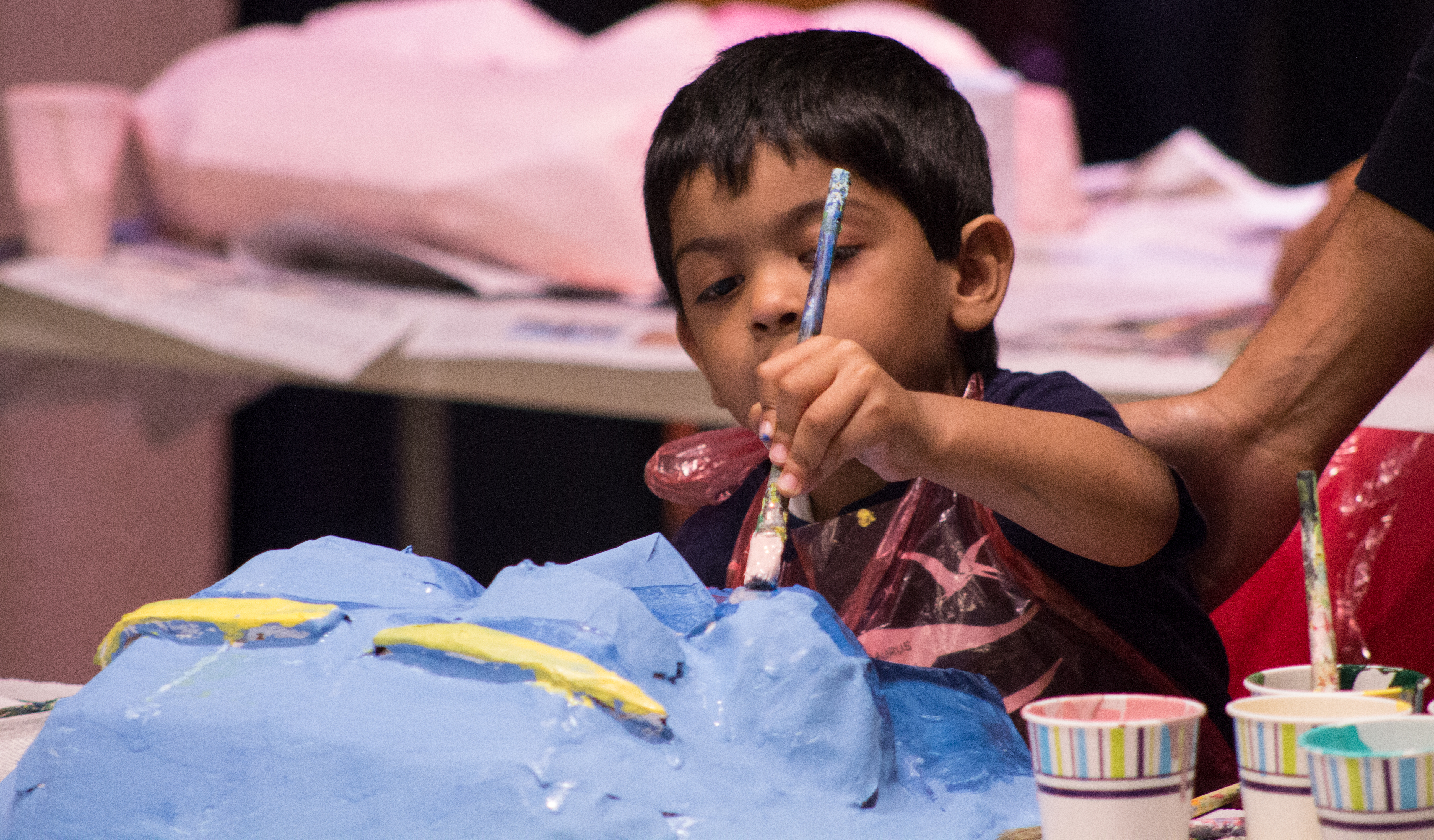 Aspiring young artist Nikhil, age 3, works on a façade of Game of Thrones' Daenerys Targaryen accompanied by his father Arun.