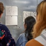 Students view draft illustrations prior to a group discussion with illustrator Dwayne Booth and Allison Paul, assistant professor of art and art history. (Peter Morenus/UConn Photo)