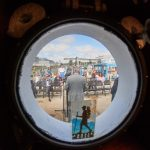 The recommissioning ceremony seen though a porthole on the R/V Connecticut. (Peter Morenus/UConn Photo)