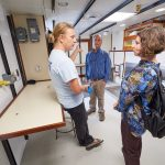 Hannes Baumann, left, assistant professor of marine sciences, speaks with Turner Cabaniss, marine and waterfront operations manager, and Zophia Baumann, assistant research professor of marine sciences, in the expanded wet laboratory space aboard the R/V Connecticut. The upgrades to the vessel included doubling the laboratory space on board. (Peter Morenus/UConn Photo)