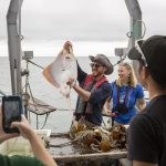 Kyle Swan, an instructor for Project Oceanology, shows off a large clearnose skate caught off the coast of Long Island Sound. (Bri Diaz/UConn Photo)