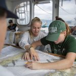 Anne Longo '20 (CLAS) and Amanda O'Lear '20 (CLAS), an environmental studies and geography major, work on a group chart navigation exercise. (Bri Diaz/UConn Photo)