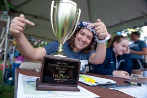 August Biondi '20 (CLAS) highlights the first place trophy the teams competed for during Learning Communities Field Day. (Defining Studios Photography for UConn)