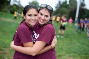 Two friends from Engineering House embrace during Learning Communities Field Day. (Defining Studios Photography for UConn)