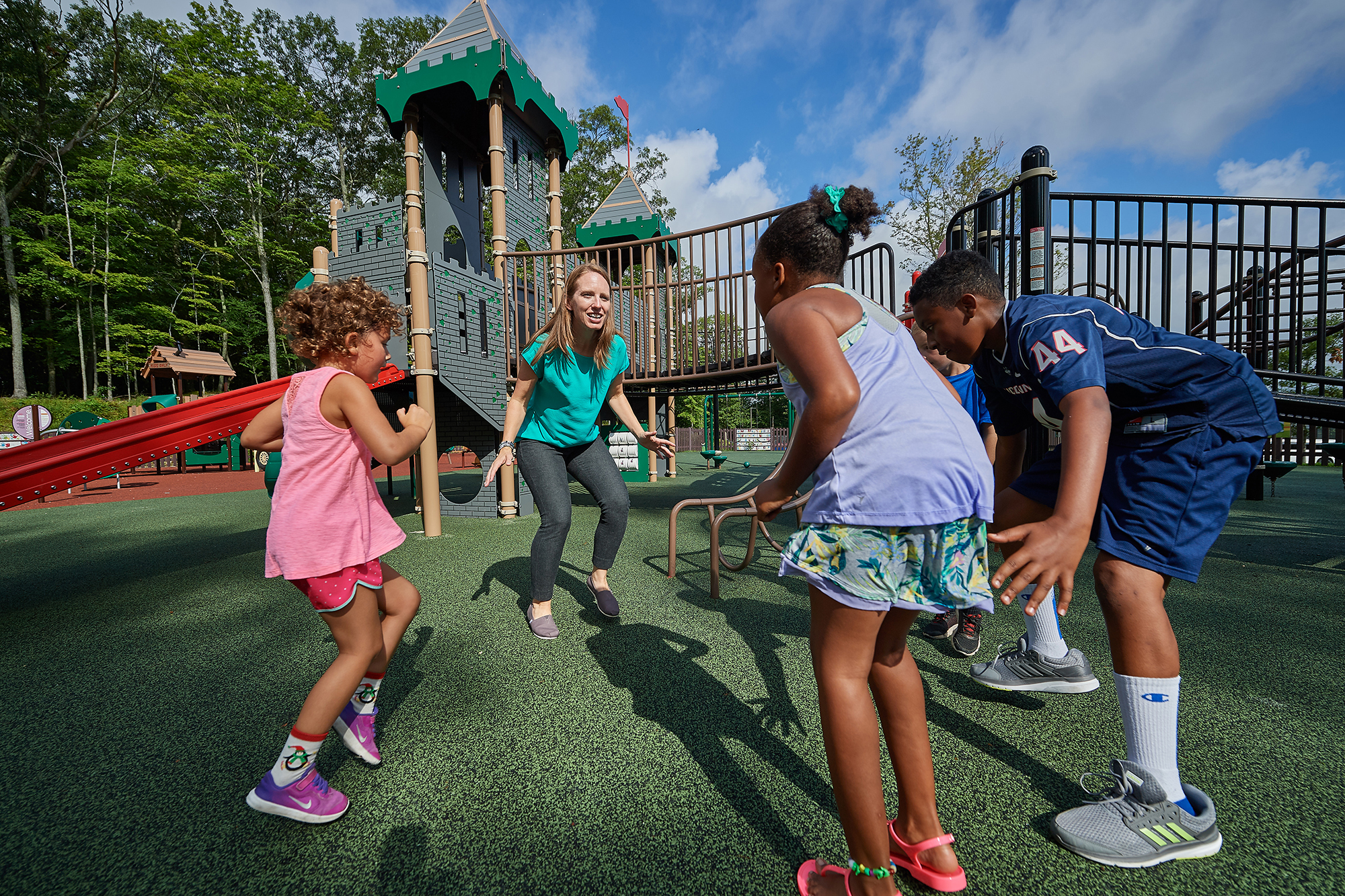 Lindsay Distefano, associate professor of kinesiology,shows children how to exercise on a playground at the Mansfield Community Center on Aug. 3, 2018. (Peter Morenus/UConn Photo)