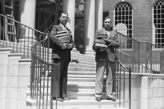 President Albert Jorgensen, left, and university librarian Paul Alcorn provided hands-on help with moving books into the new library in 1940. The building was named for former Connecticut governor Wilbur Cross in 1942. (University Library Archives & Special Collections)