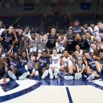 The UConn Men's and Women's Basketball Teams pose for a group shot, together with the two youngsters (front row) from Team IMPACT whom the teams have 'adopted.' (Stephen Slade '89 (SFA) for UConn)