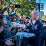 In preparation for First Night, Men's Basketball head coach Dan Hurley distributes pizza to fans waiting in line outside Gampel Pavilion. (Jason Reider/UConn Athletics Photo)