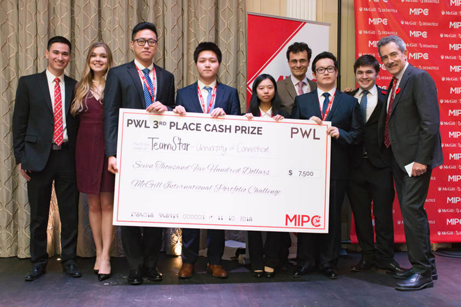 UConn students, from left, Junchao Liao, Xiofan Hou, Xiao Wang and Tuershunjiang Ahemaitijiang hold their check after being recognized as the top U.S. team at the McGill International Portfolio Challenge in Montreal earlier this month. They are surrounded by event organizers. (Photo Courtesy of Jose Aponte)