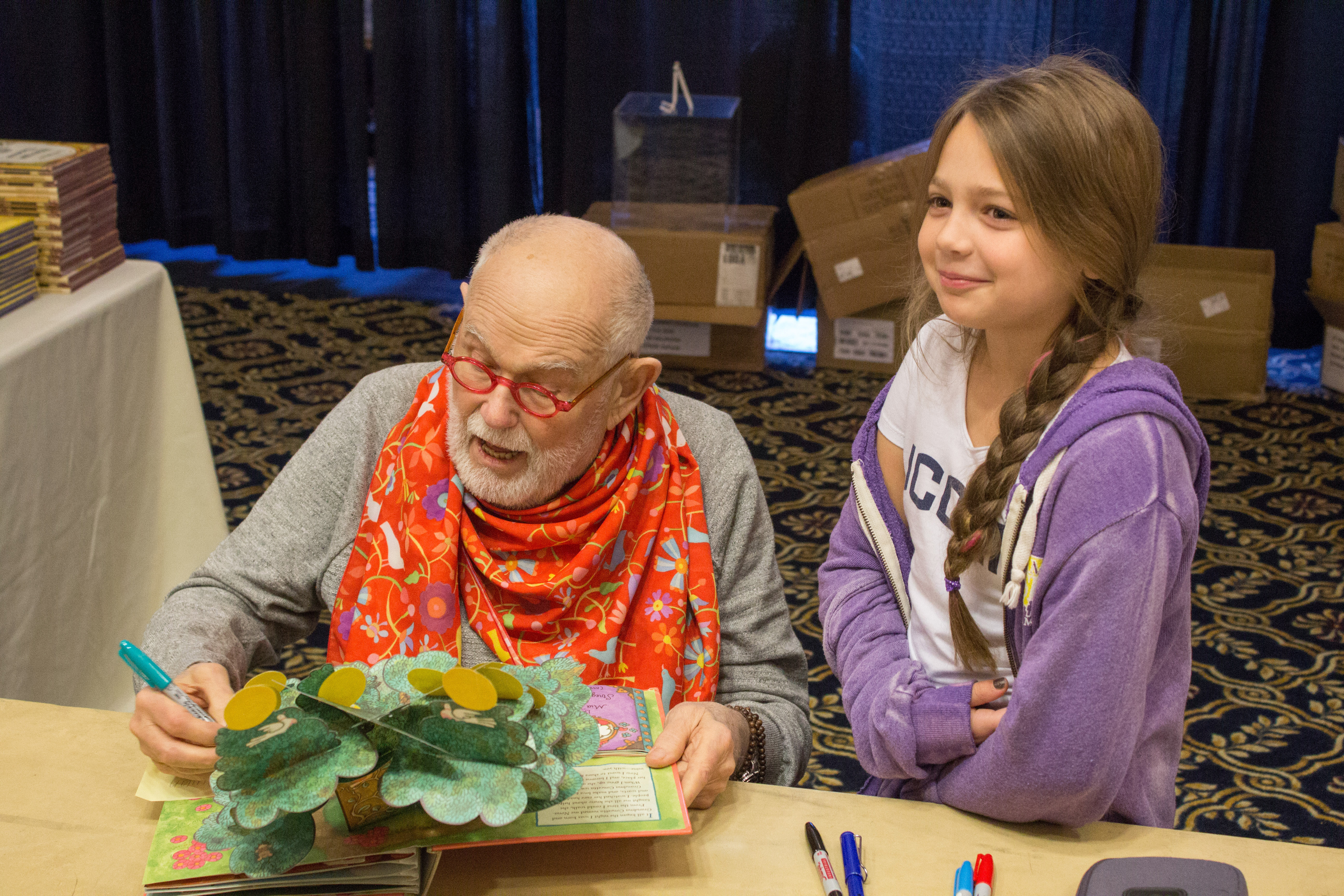 Renowned children's book author Tomie dePaola signs Quinn Ostergren's copy of his popup book 'Brava, Strega Nona!' (Lucas Voghell '20 (CLAS)/UConn Photo)