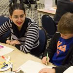 Neda Izadi '21 (SFA) shows Alex Rastelli, 9, how to make puppets out of manila folders. (Lucas Voghell '20 (CLAS)/UConn Photo)