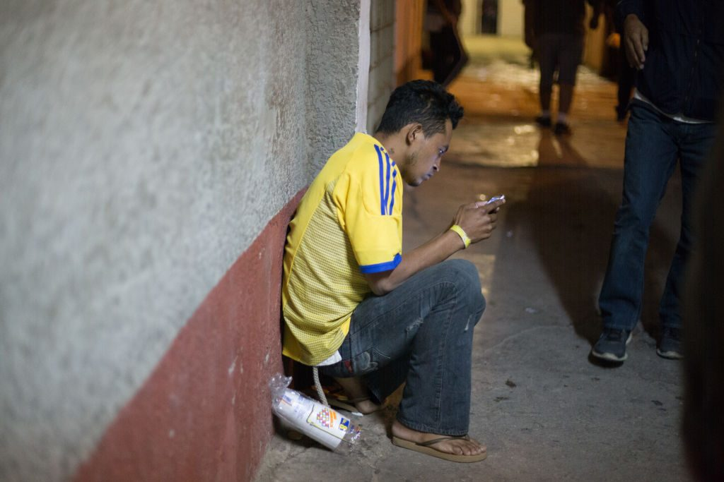 In Mexicali, Mexico, a migrant uses his cellphone. (Photo by Luis Boza/VIEWPress/Corbis via Getty Images)