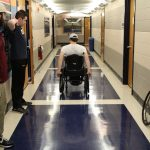 Senior biomedical engineering majors Mitchell DuBuc, James Welch, and Alex Draper, under the advisement of Professor Krystyna Gielo-Perczak, are putting a new type of wheelchair wheel to the test for their Senior Design project. Here, Mitchell DuBuc, center, a wheelchair user, tests the new wheels in the Arthur B. Bronwell Building. (Eli Freund/UConn Photo)