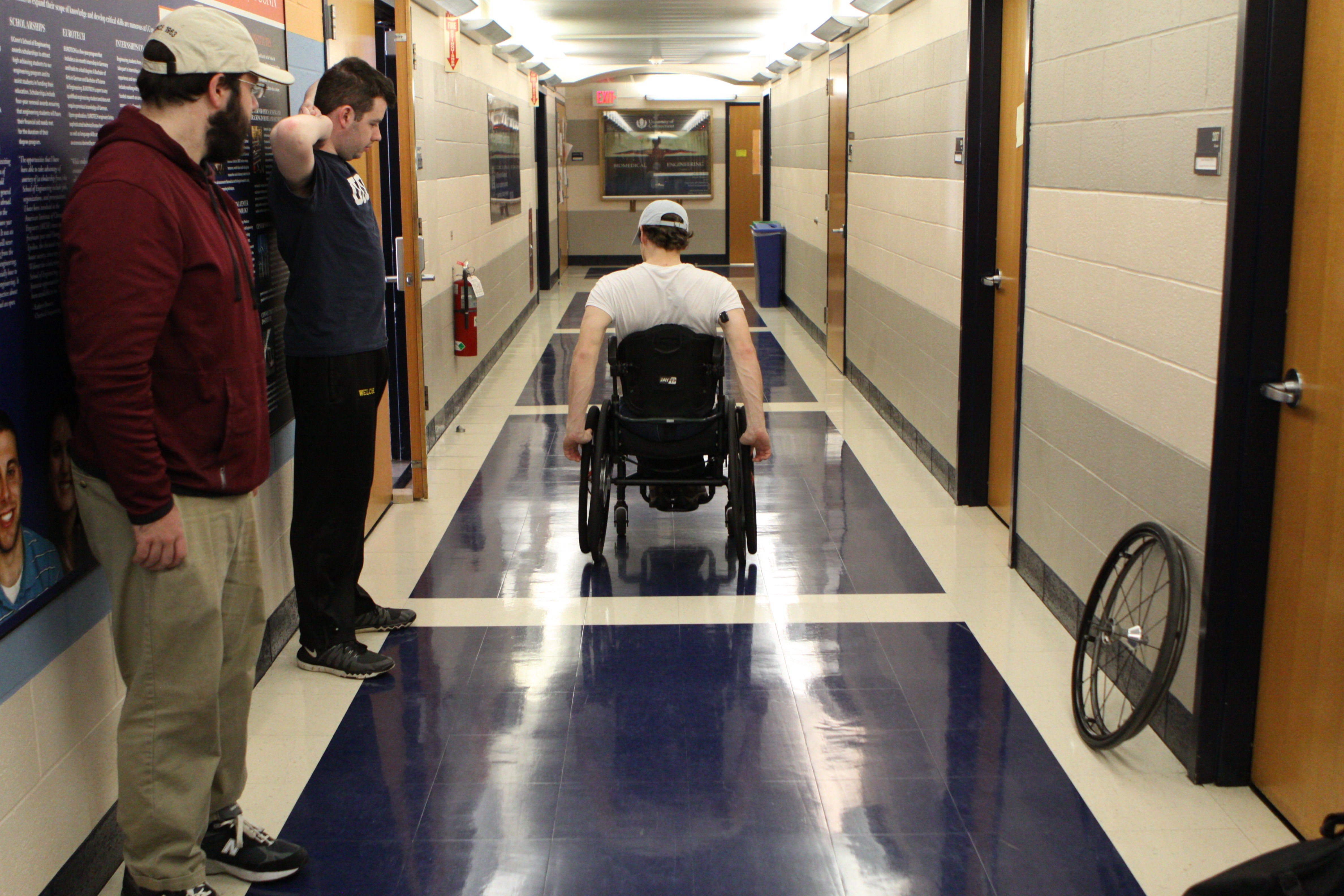 Mitchell DuBuc, center, tests the new wheels in the Arthur B. Bronwell Building at UConn. (Eli Freund/UConn Photo)