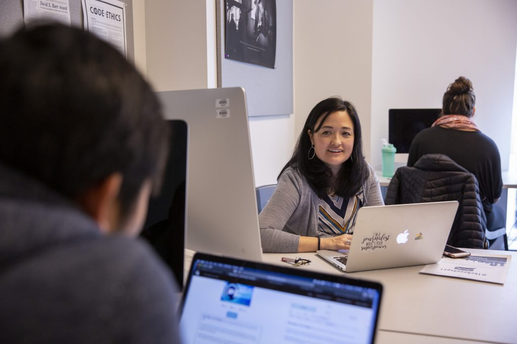 Marie Shanahan, associate professor of journalism, works with students in her JOUR 4016: Publication Practice course on Nov. 1, 2018. (Bri Diaz/UConn Photo