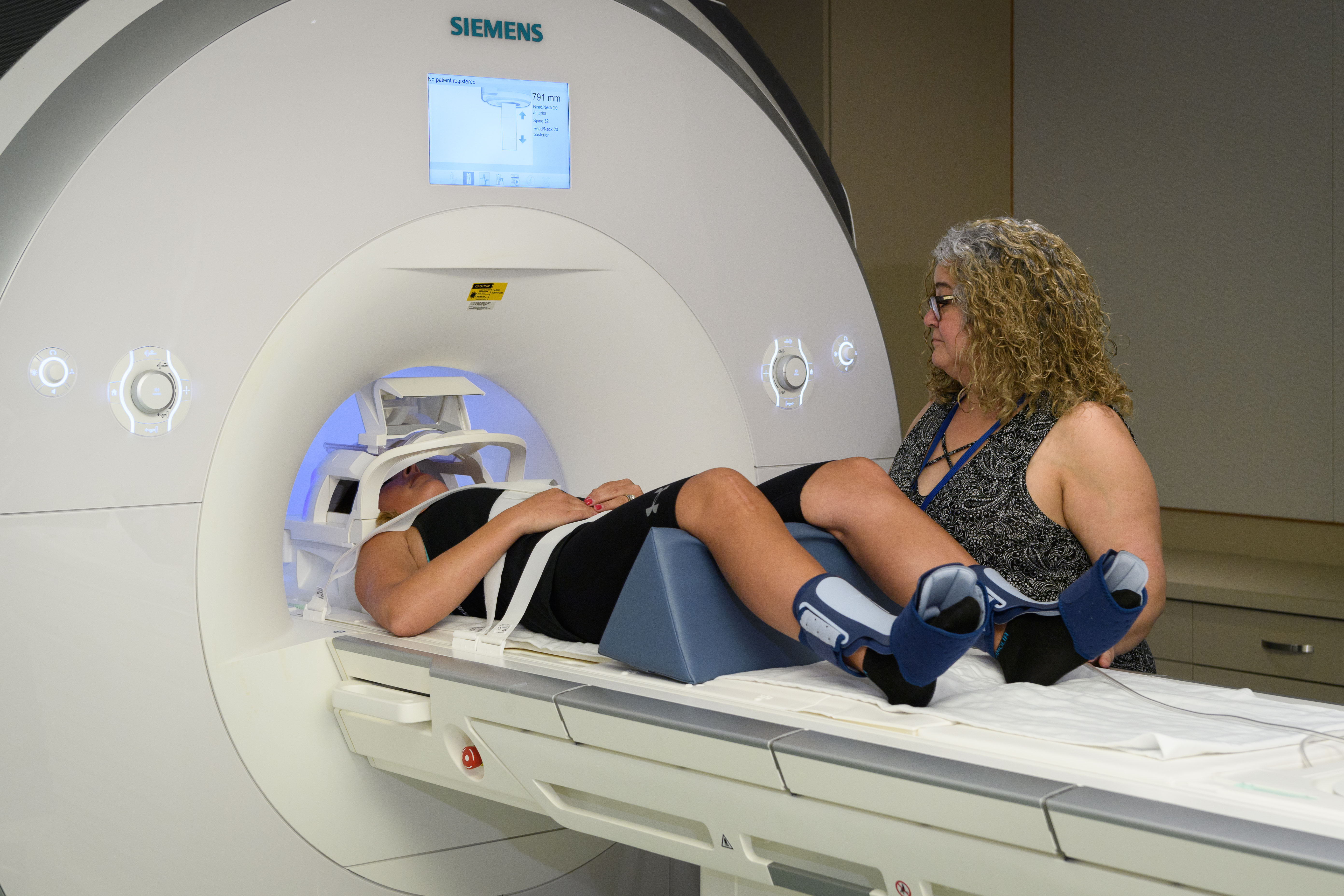 MRI service manager Elisa Medeiros prepares a patient for functional MRI testing at the BIRC in the Phillips Communication Sciences Building. (Peter Morenus/UConn Photo)
