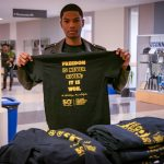 This year's Kwanzaa celebration was one of many events marking the 50th anniversary of the African American Cultural Center. Here, Mekhi Amos '21 (BUS) holds up an anniversary t-shirt outside the Student Union Ballroom. (Lucas Voghell '20 (CLAS)/UConn Photo)