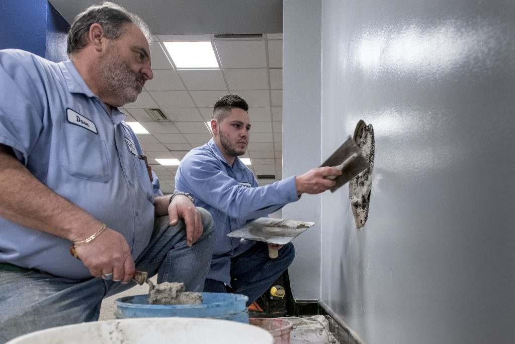 Longtime UConn mason Dave Prouty, left, looks on as 'new guy' Connor Adams, a UConn employee since 2017, repairs a wall in Shippee Hall. (Sean Flynn/UConn Photo)