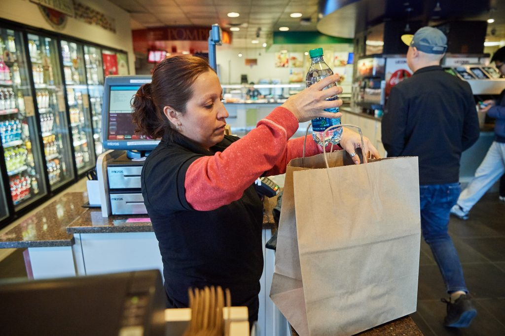 Patricia Ruffino, a cashier at the Union Street Market, fills a paper bag with a purchase. (Peter Morenus/UConn Photo)