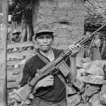 A rebel militiaman hoists his rifle in a gesture of defiance in front of his home in rebel-occupied Chalatenango Department, El Salvador, 1984. (Scott Wallace)