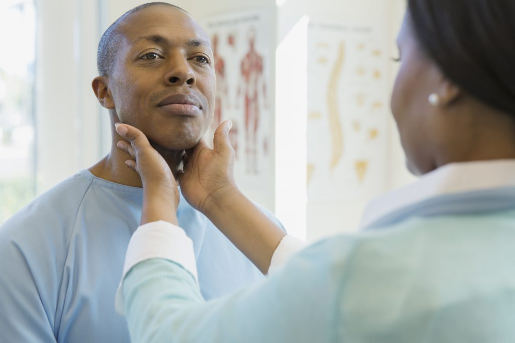 An African American female doctor examines an African American male patient in the clinic. The HDI report card recommends that Connecticut bring more people of color into health care services delivery. (Getty Images)