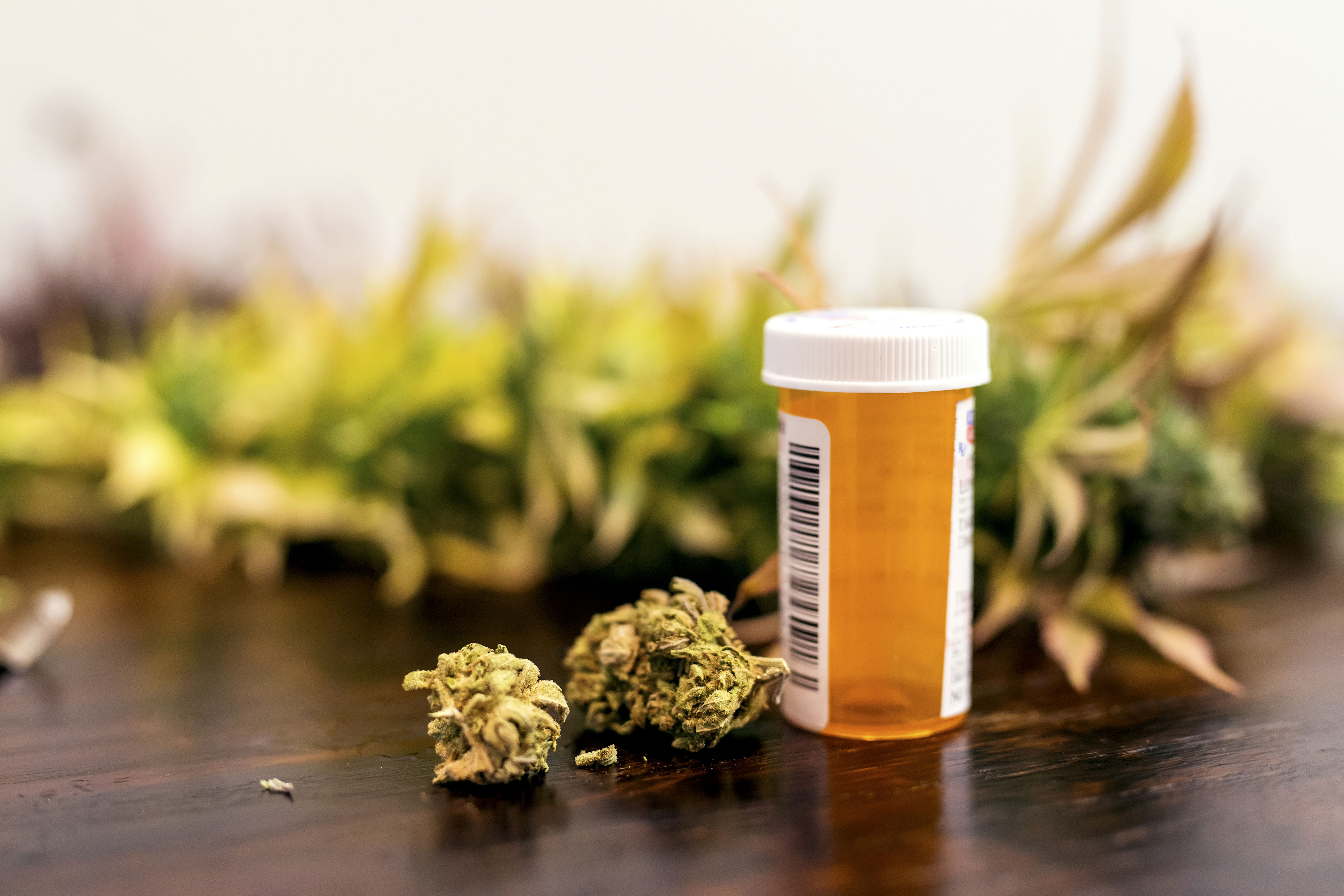 Marijuana buds sitting next to prescription medicine bottle. (Getty Images)