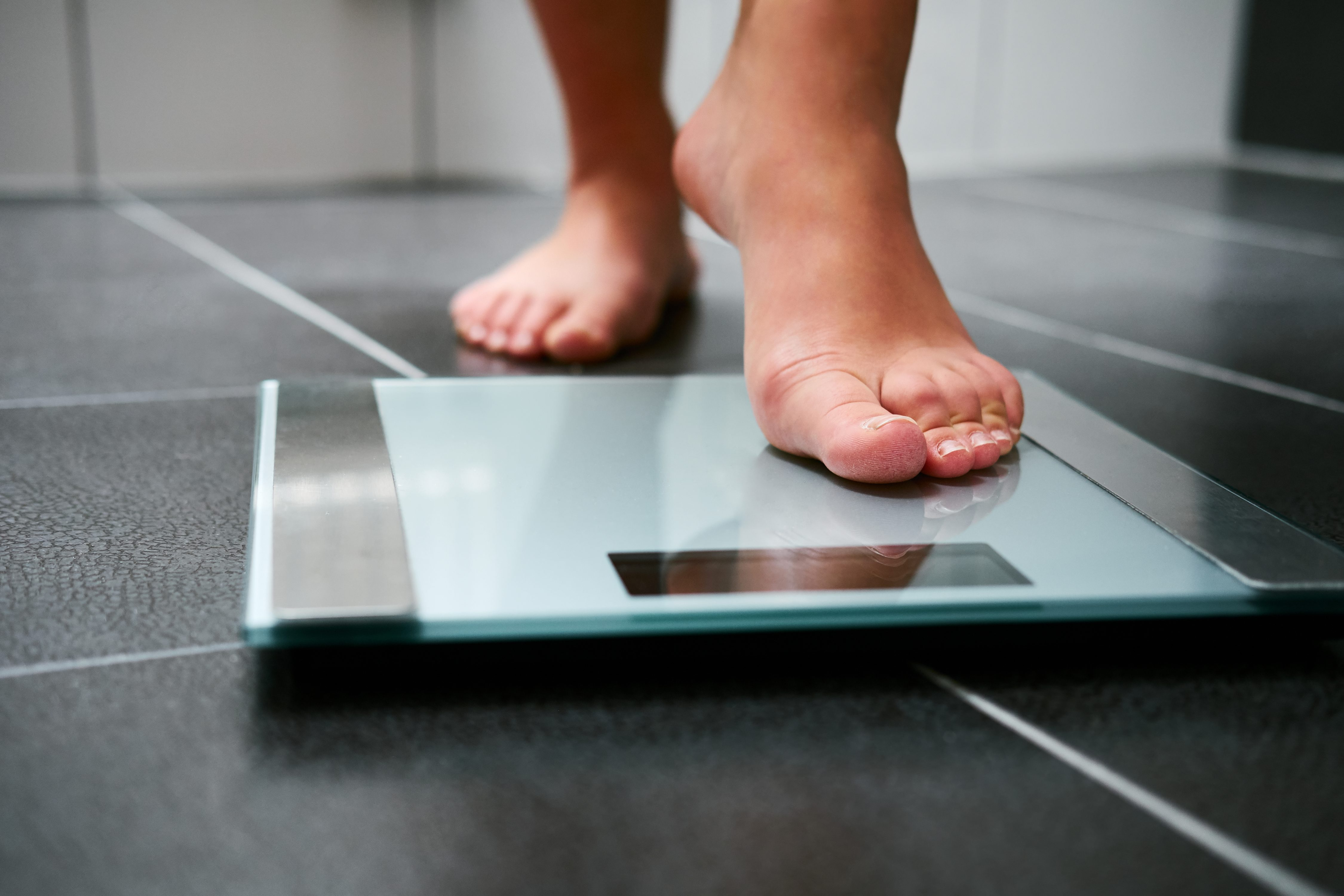 Female bare feet with weight scale in the bathroom. (Getty Images)