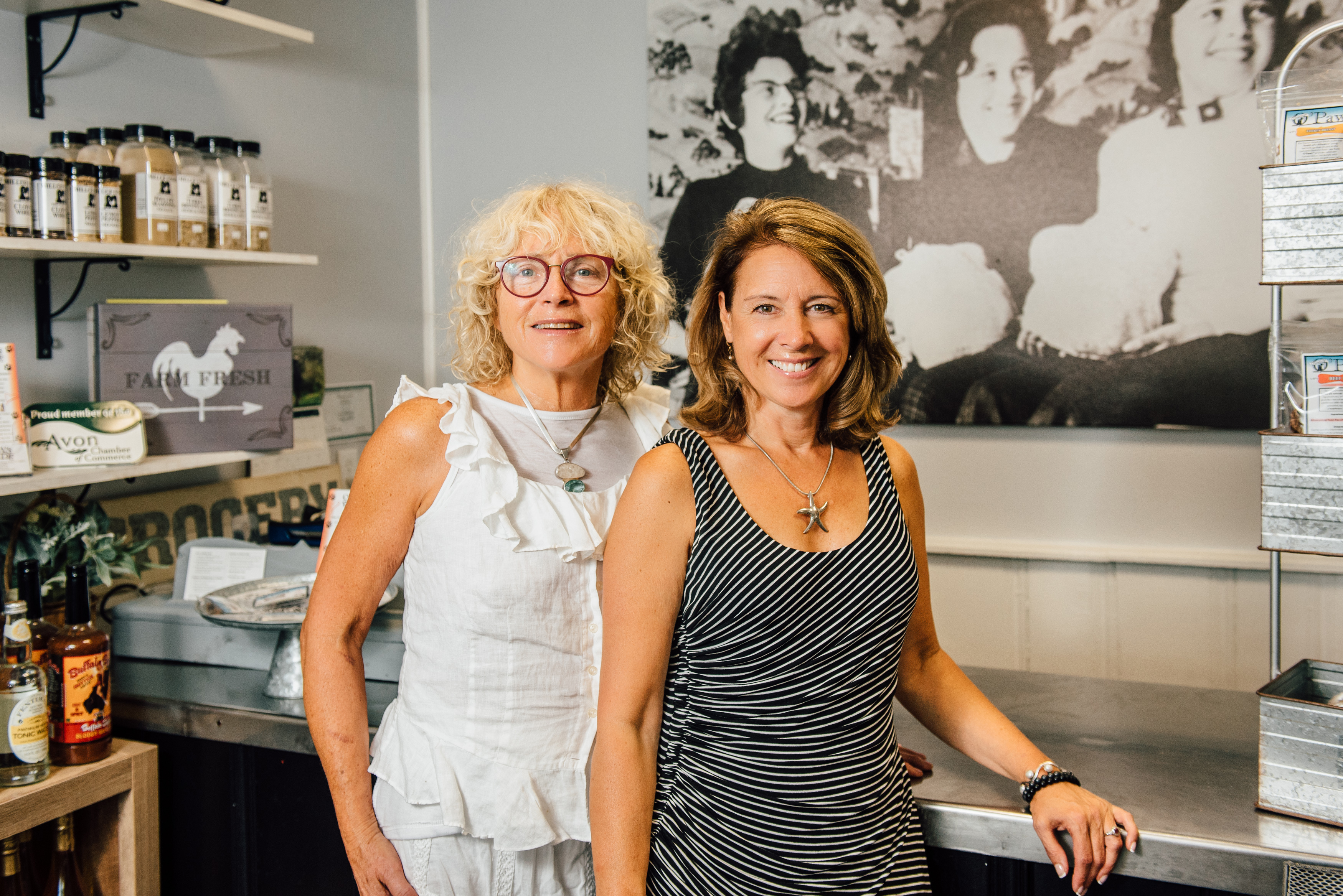 Cal Miller-Stevens, left, and her niece Capri Frank pose for a photo inside the store at Miller Foods Inc., a fourth-generation, family-owned and operated food business located in Avon, Connecticut. Behind them is a photo taken in the early 1960s, in the same location. From left is family matriarch Margaret 'Oma' Miller and her two daughters, Sandi Trudeau (Frank's mother) and Miller-Stevens. (Nathan Oldham/UConn Photo)