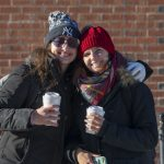 Friendship and hot coffee help keep out the cold for these students, pictured outside the Student Union. (Sean Flynn/UConn Photo)