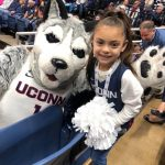 Daniela poses for a photo with the Husky mascot.