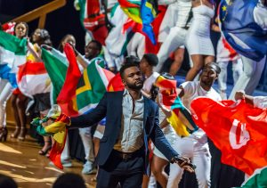 The host, Mr. Cocoyam, foreground, with Chidubem Onochie '21 (NUR), right, and other members of the cast modeling the flags of African countries. (Lucas Voghell '20 (CLAS)/UConn Photo)