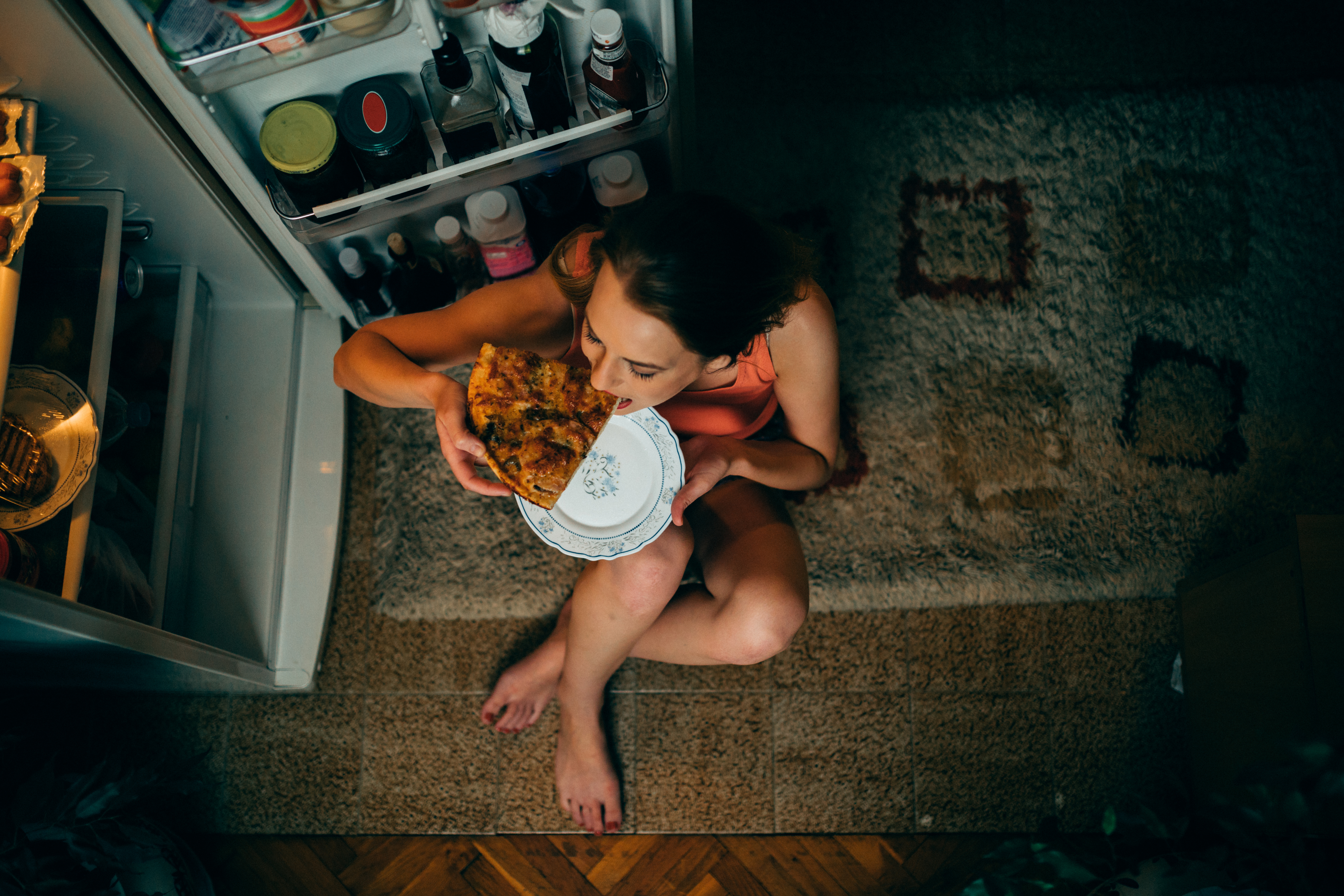 A young woman eating pizza in front of the refrigerator late at night. (Getty Images)