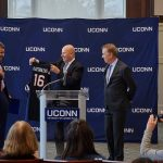 Thomas Katsouleas, left, reacts as he is presented with a basketball jersey by board chair Thomas Kruger, center, and Gov. Ned Lamont at a press conference following his appointment to be the 16th president of the University of Connecticut on Feb. 5, 2019. (Peter Morenus/UConn Photo)