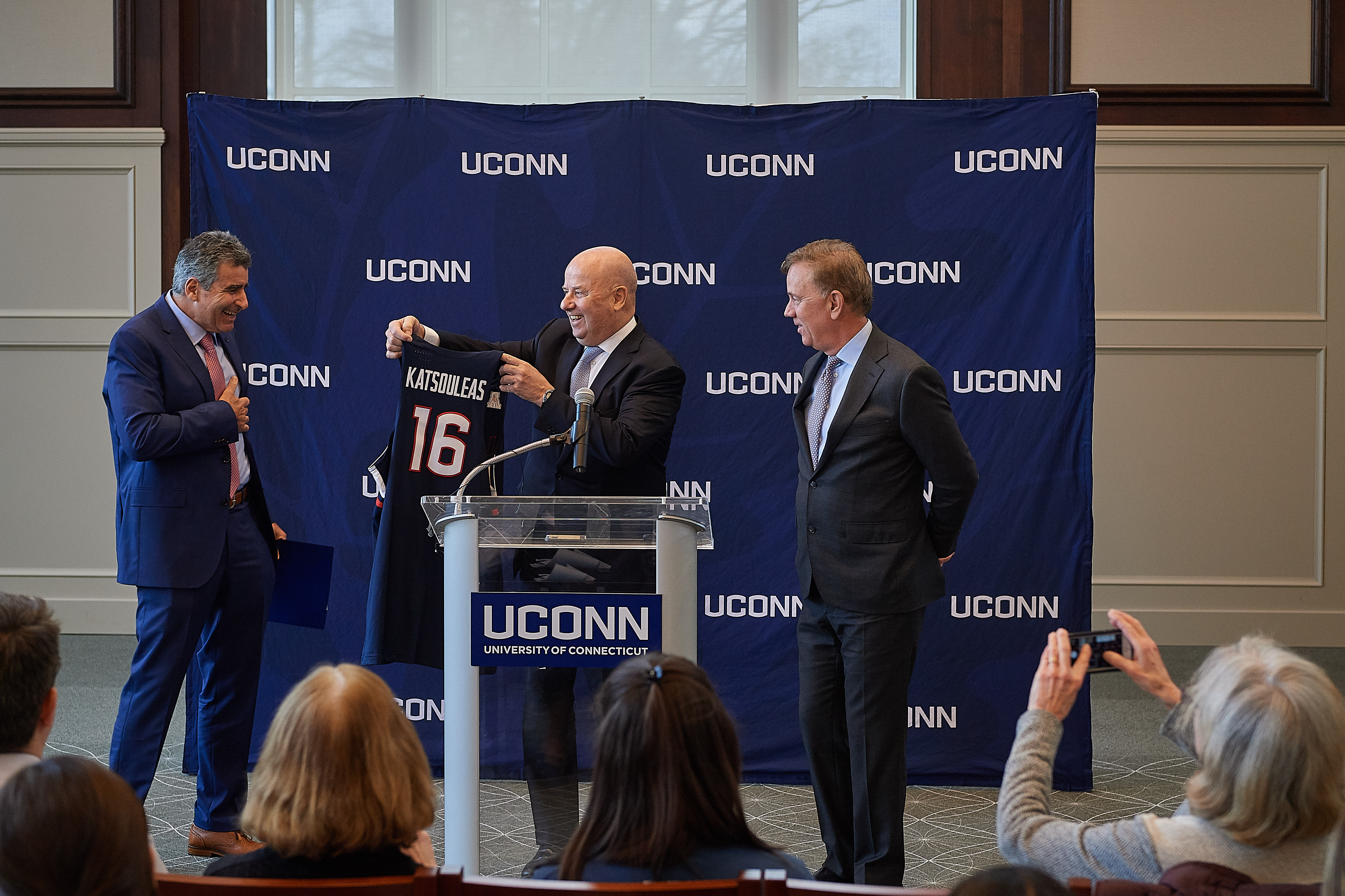 Thomas Katsouleas, left, reacts as he is presented with a basketball jersey by board chair Thomas Kruger, center, and Gov. Ned Lamont at a press conference following his appointment to be the 16th president of the University of Connecticut. (Peter Morenus/UConn Photo)