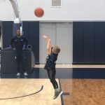 Rylan takes a shot on the practice court at the Werth Family Basketball Champions Center, as Taliek Brown, director of student-athlete development, looks on. (UConn Men's Basketball Photo)