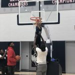 Mamadou Diarra helps Rylan reach the basket on the practice court at the Werth Family Basketball Champions Center, as Eric Cobb looks on, and Alterique Gilbert, far left, snaps a photo. (UConn Men's Basketball Photo)