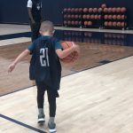 Alterique Gilbert encourages Rylan as he warms up on the practice court at the Werth Family Basketball Champions Center. Rylan is wearing a jersey with Mamadou Diarra's number, 21. (UConn Men's Basketball Photo)