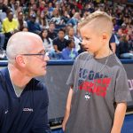 Head Coach Dan Hurley engages Rylan in conversation on the court at Gampel Pavilion during First Night on Oct. 12, 2018. (Stephen Slade '89 (SFA) for UConn)
