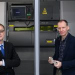Pamir Alpay, left, and Rainer Hebert,  stand next to a 3D metal printer at the Innovation Partnership Building onDec. 20, 2017. (Peter Morenus/UConn Photo)