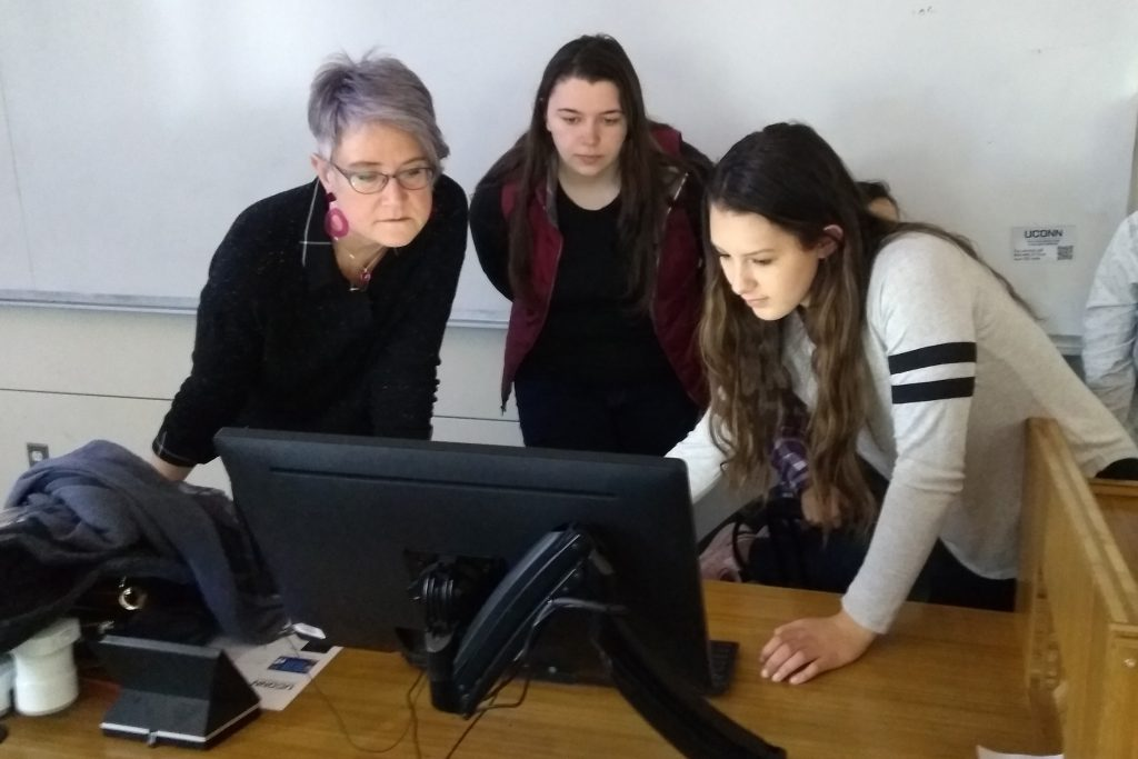From left, Kelly Dennis, professor of art and art history; Megan Scholtz, '19 (SFA), a photography major; and Deanna LaVoie '20 (SFA), graphic design major, reviewing an updated biography in preparation for this year's Art + Feminism Edit-a-thon during a History of Photography class in Oak Hall. (Kenneth Best/UConn Photo)
