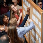 Medical students pick envelopes containing their residency assignment from bulletin boards during the match day ceremony held in the Academic Atrium at UConn Health in Farmington on March 15, 2019. (Peter Morenus/UConn Photo)