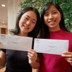 Medical students Katherine Tian, left, Katelyn Wong show off the envelopes before opening them at the residency Match Day ceremony held in the Academic Atrium at UConn Health in Farmington on March 15, 2019. (Peter Morenus/UConn Photo)