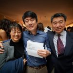 Kyle Shin, center, with his parents Eun-Ju Shin, right, visiting professor of literature, cultures and languages and Dong-Kuk Shin, professor of computer science and engineering, following the residency match day ceremony held in the Academic Atrium at UConn Health in Farmington on March 15, 2019. (Peter Morenus/UConn Photo)