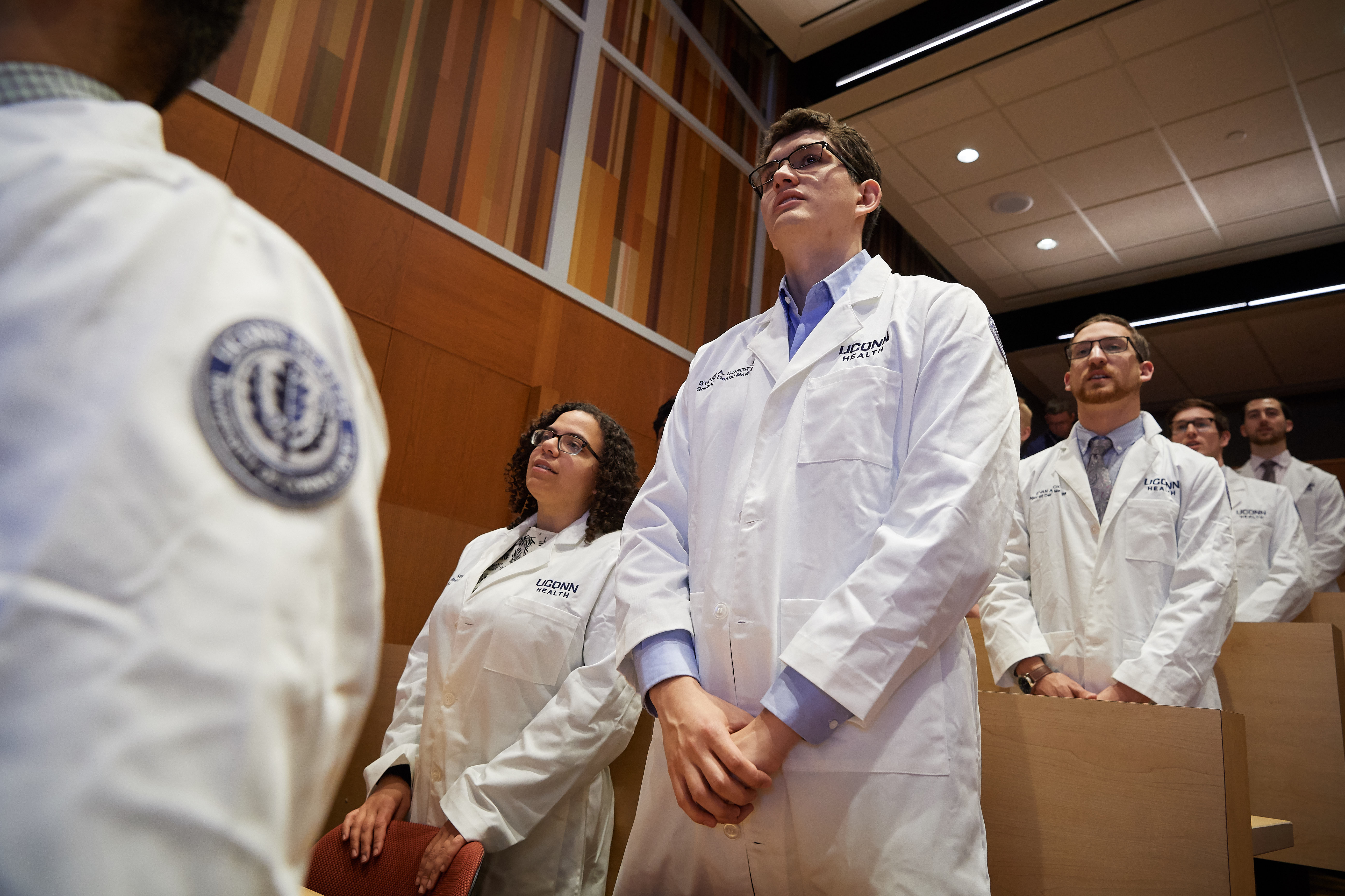 Second year dental students recite an American Dental Association pledge during a white coat ceremony on Friday marking their transition from theoretical to clinic-based learning. (Peter Morenus/UConn Photo)