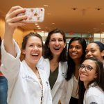 Julia Lafen, left, and other second year dental students pose for a selfie at the UConn Health academic atrium after their white coat ceremony. (Peter Morenus/UConn Photo)