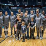 Daniela with the Women's Basketball team and family members on Junior Husky Club day at Gampel Pavilion on Jan. 27, 2019: her mom, Nicole, and dad, Daniel, sister Angelina (10), brother Dominic (12), and, in the arms of Batouly Camara, brother Matteo (2). (Jason Reider/Athletic Marketing Photo)