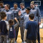 Daniela gives a high five, as members of the Women's Basketball team and Daniela's family look on, on Junior Husky Club day at Gampel Pavilion on Jan. 27, 2019. From left, her mom, Nicole, sister Angelina (10), and brother Dominic (12). (Jason Reider/Athletic Marketing Photo)