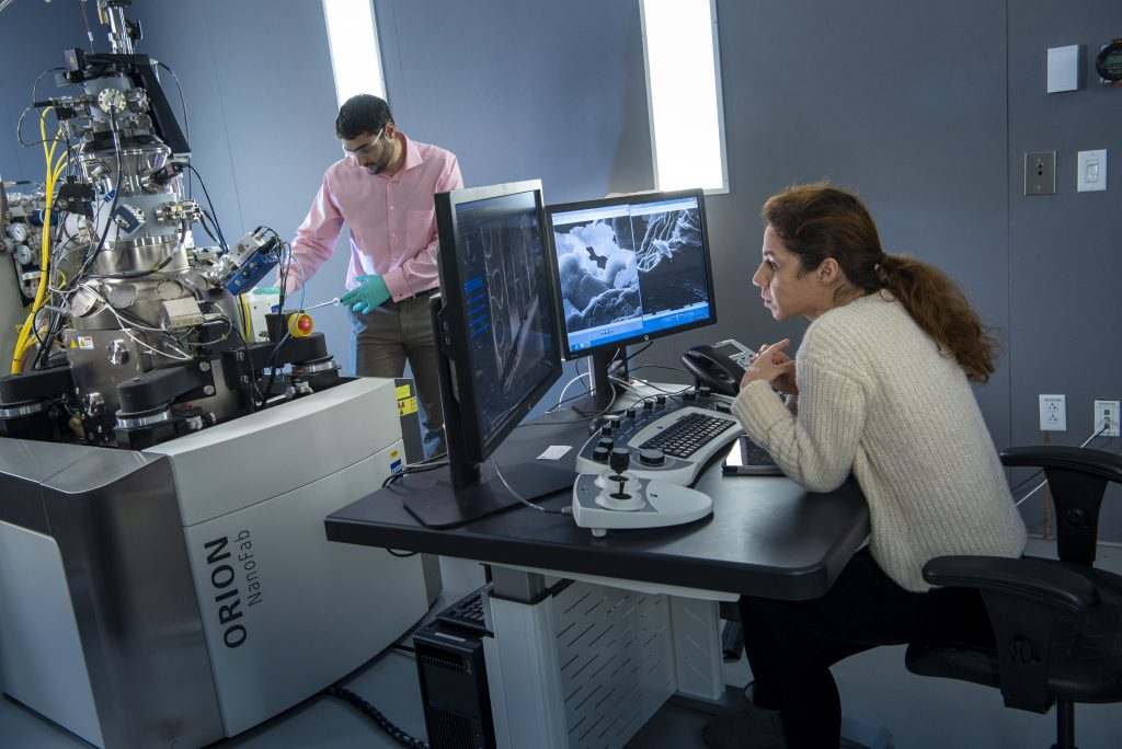 Nicholas May and Bahar Ahmadi work with the ZEISS Orion NanoFab Helium Ion Microscope. (Al Ferreira/UConn Photo)