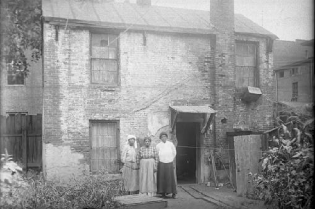 Three African-American women stand in front of east side tenements on Pearl Street in Hartford, circa 1900-1920. (Courtesy of the Hartford History Center, Hartford Public Library)