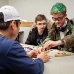 Junior UConn Engineering student Brian Santivanez, foreground, helps Brandon Rutowski (back left) and Joshua Levesque of HALS Academy in New Britain make their own 'windmill,' to learn about the connection between electricity and magnetism. (Christopher LaRosa/UConn Photo)